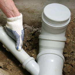 Plumber installing new PVC sewage drain pipes