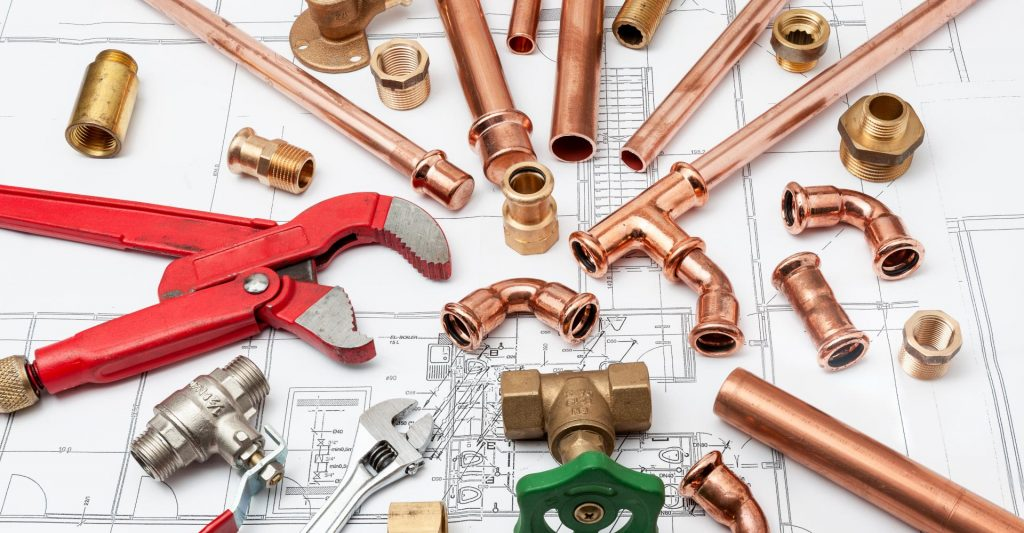 Plumbing parts and plumber tools laid over housing plans
